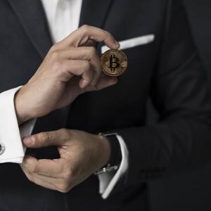 コインを持つスーツの男性