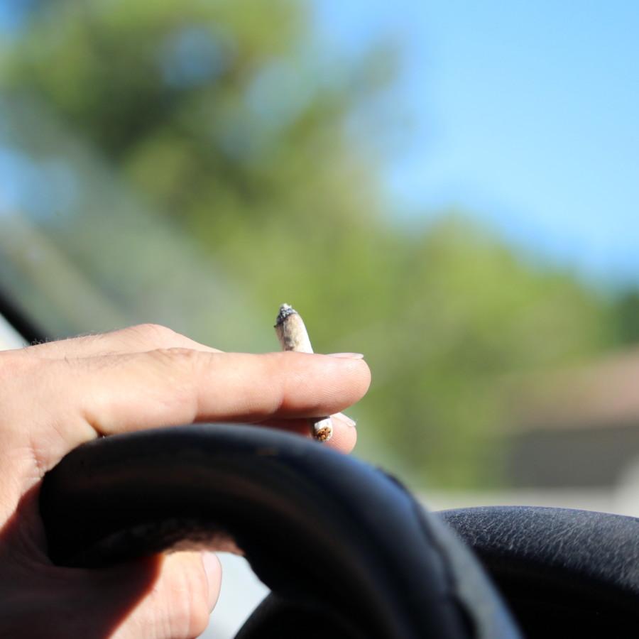 運転中に大麻を吸う男性の手