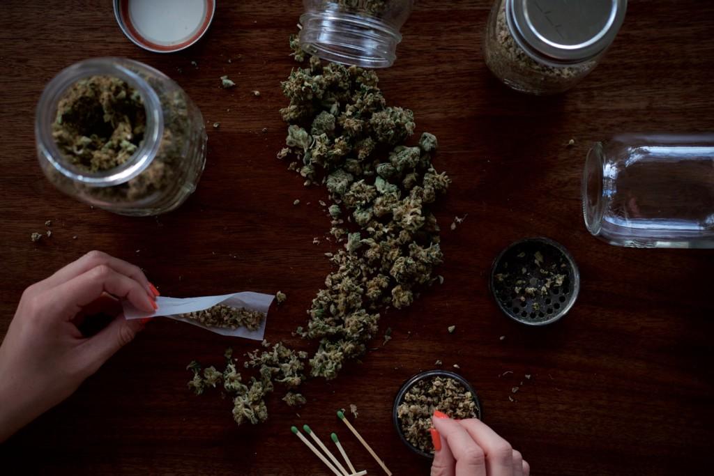 大麻とジョイントを巻く男性の手