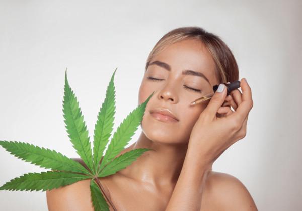 大麻草とCBDオイルを顔に塗る女性