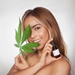 大麻草とCBDオイルを持つ美女